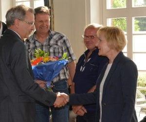 """Staatssekretär Hendrik Fischer beglückwünscht Rosemarie Bredemann als Vertreterin von Geierswalde zum 2. Platz """"Kollektivgeschichten"""""""