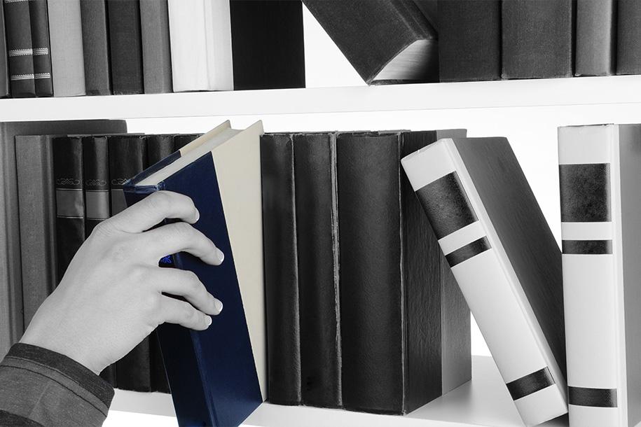 Eine Person nimmt sich ein farblich hervorgehobenes Buch von einem Regal – Rohnstock Biografien